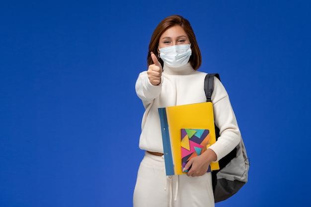 青い壁にバッグとコピーブックとマスクを身に着けている白いジャージの正面図若い女子学生