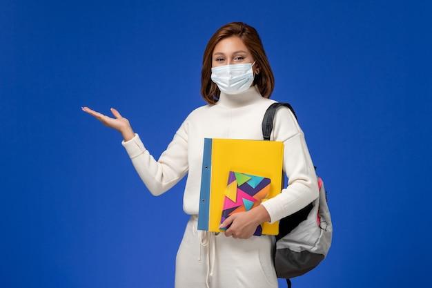 Вид спереди молодая студентка в белом джерси в маске с сумкой и тетрадями на синей стене