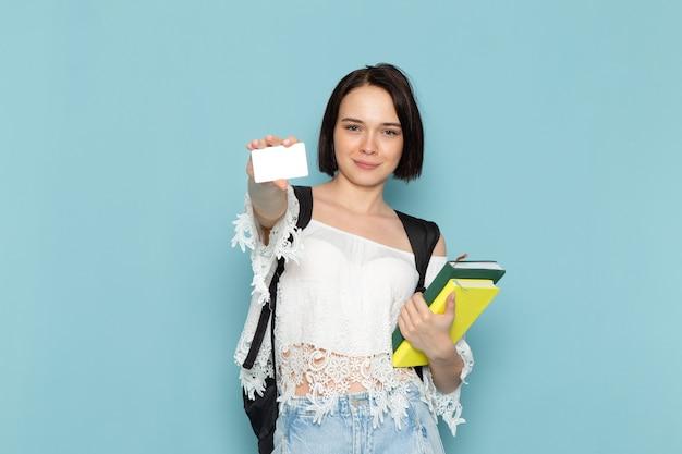 Вид спереди молодая студентка в белой рубашке, синих джинсах и черной сумке, держащая тетради и карточку на синем пространстве студентка