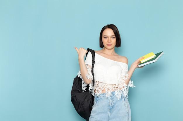 白いシャツブルージーンズと青いスペースのコピーブックを保持している黒いバッグの正面の若い女性学生女子学生大学が学校を教える