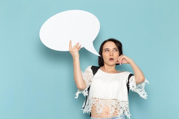 白いシャツのブルージーンズと青い空間女子大生を考えて巨大な白い看板を持っている黒いバッグの正面の若い女子学生