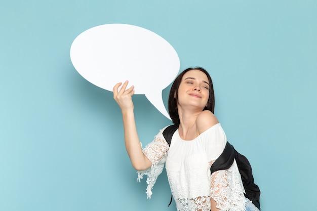 白いシャツブルージーンズと青い空間の女子学生大学校に白い巨大な看板を持っている黒いバッグの正面の若い女子学生
