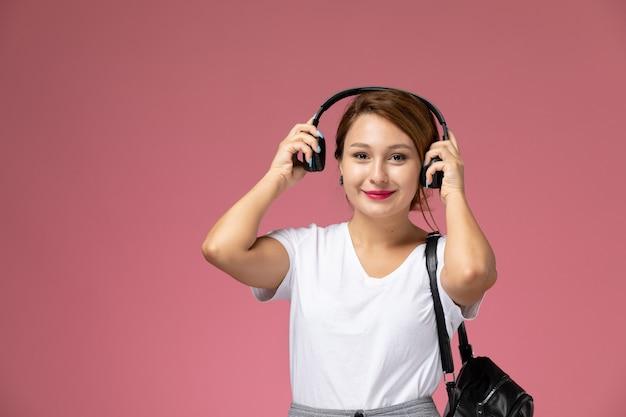 ピンクの背景のレッスン大学大学で笑顔で音楽を聴いている白いtシャツと灰色のズボンの正面図若い女子学生