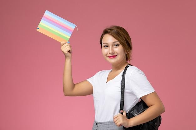 ピンクの背景のレッスン大学大学で彼女の手にコピーブックを持つ白いtシャツと灰色のズボンの正面図若い女子学生