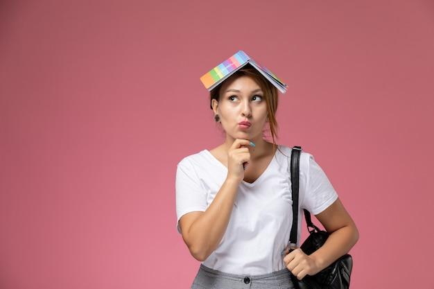 Вид спереди молодая студентка в белой футболке и серых брюках с тетрадкой на голове и думающим выражением лица на розовом столе уроки университетского колледжа