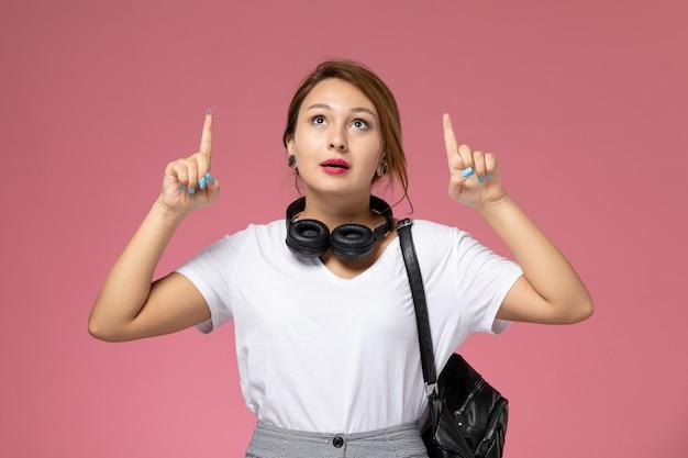 분홍색 배경 학생 수업 대학 대학에 하늘을보고 이어폰 흰색 티셔츠와 회색 바지에 전면보기 젊은 여성 학생