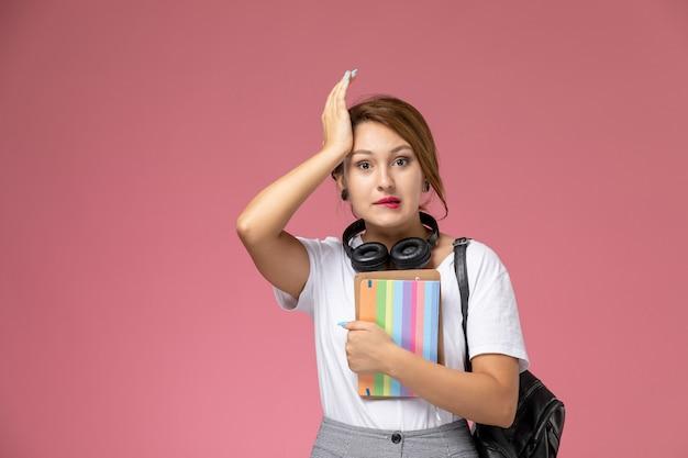 ピンクの背景の学生レッスン大学大学で彼女の手にヘッドフォンとコピーブックと白いtシャツと灰色のズボンの正面図若い女子学生