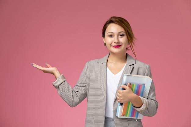 분홍색 책상에 미소를 그녀의 손에 카피 북과 흰색 티셔츠 회색 코트와 회색 바지에 전면보기 젊은 여성 학생 대학 대학 연구