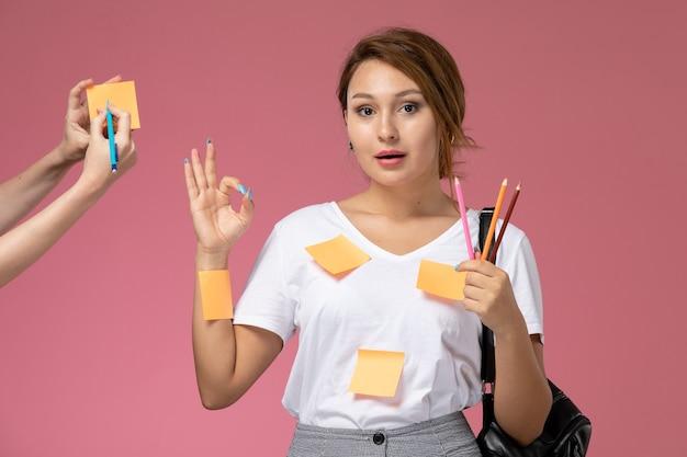 Вид спереди молодая студентка в белой футболке с карандашами на розовом фоне уроки университетского колледжа
