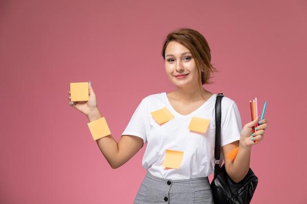 Вид спереди молодая студентка в белой футболке, улыбаясь, держит карандаши на розовом фоне, учебные книги университетского колледжа