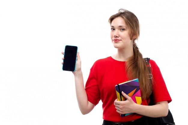 Una giovane studentessa di vista frontale negli archivi rossi dei quaderni della tenuta della borsa del nero della camicia che sorride tenendo il suo telefono sul bianco