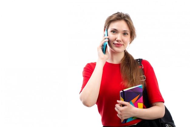 Una giovane studentessa di vista frontale negli archivi rossi dei quaderni della tenuta della borsa del nero della camicia che sorride facendo uso del suo telefono sul bianco
