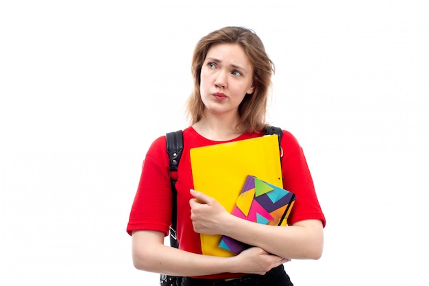 A front view young female student in red shirt black bag holding copybooks files thinking on the white