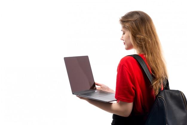 Una giovane studentessa di vista frontale nella borsa rossa del nero della camicia facendo uso del computer portatile sul bianco