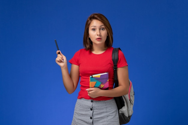 Front view young female student in red shirt wearing backpack holding copybook on the blue background.