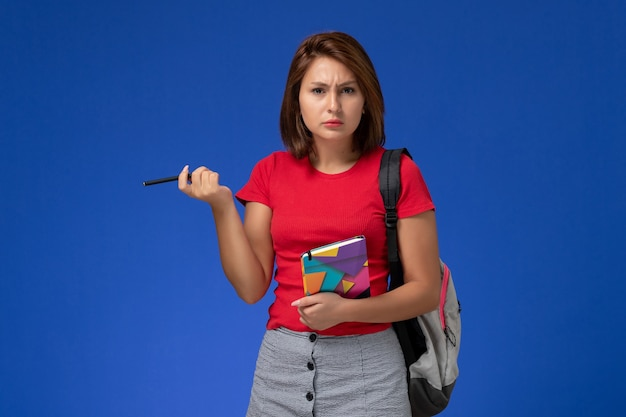 Front view young female student in red shirt wearing backpack holding copybook on light-blue background.