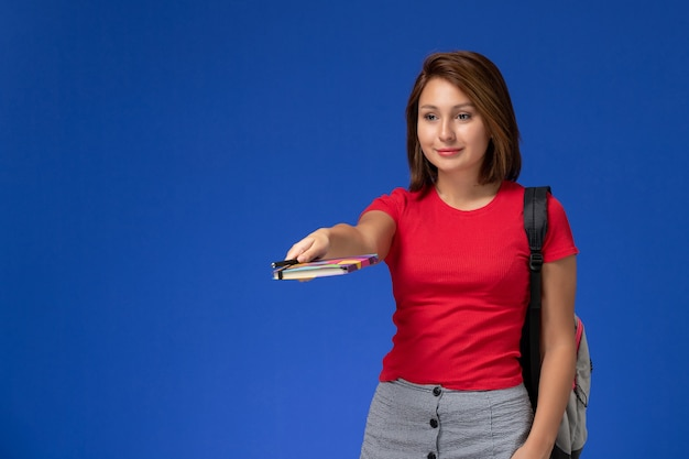 Front view young female student in red shirt wearing backpack holding copybook with pen on the blue background.