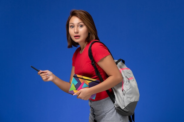 Front view young female student in red shirt wearing backpack holding copybook with pen on light-blue background.