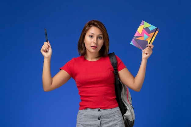 Front view young female student in red shirt wearing backpack holding copybook with pen on light blue desk.