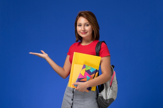 Front view young female student in red shirt wearing backpack holding files and copybook on the blue background.