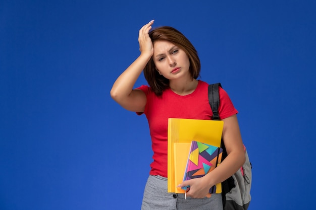 Front view young female student in red shirt wearing backpack holding files and copybook having headache on blue background.