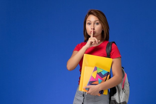 Front view young female student in red shirt wearing backpack holding files and copybook on light blue background.