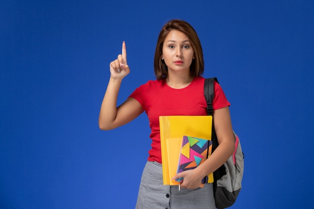 Front view young female student in red shirt wearing backpack holding files and copybook on the light blue background.