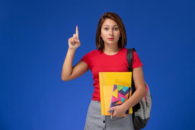 Giovane studentessa di vista frontale in camicia rossa che indossa lo zaino che tiene i file e il quaderno sullo sfondo azzurro.
