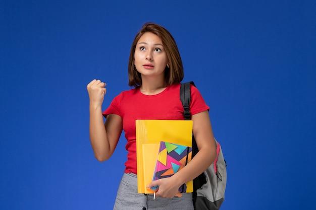 Vista frontale giovane studentessa in camicia rossa che indossa uno zaino in possesso di file e quaderno che si rallegra su sfondo blu.