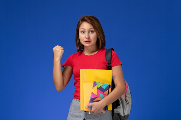 Front view young female student in red shirt wearing backpack holding files and copybook rejoicing on blue background.