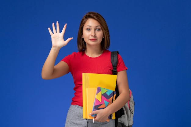 Front view young female student in red shirt wearing backpack holding files and copybook showing her palm on blue background.