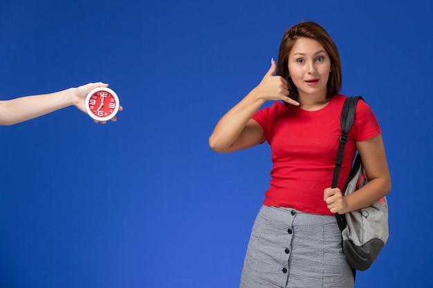 Vista frontale giovane studentessa in camicia rossa che indossa uno zaino che mostra la telefonata posa su sfondo azzurro.