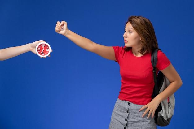 Vista frontale giovane studentessa in camicia rossa che indossa uno zaino minaccia su sfondo azzurro.