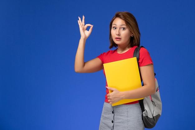 Vista frontale giovane studentessa in camicia rossa con zaino in possesso di file gialli su sfondo azzurro.