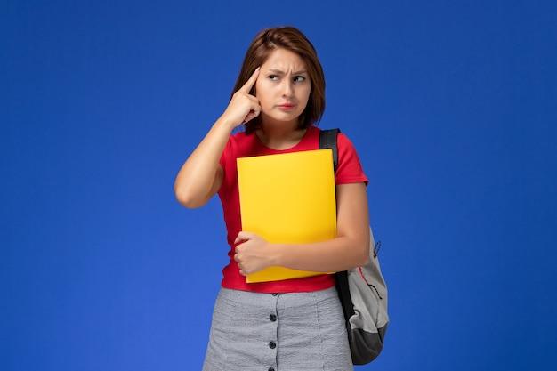 Vista frontale giovane studentessa in camicia rossa con zaino in possesso di file gialli e pensando su sfondo azzurro.
