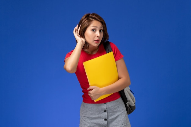 Front view young female student in red shirt with backpack holding yellow files trying to hear on light-blue background.