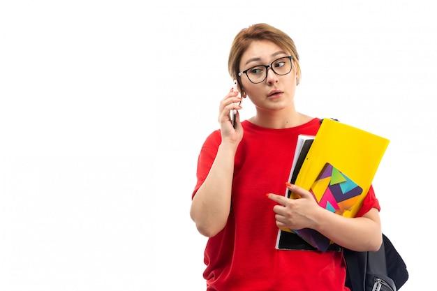Una giovane studentessa di vista frontale in jeans neri della maglietta rossa che tengono i quaderni che parlano sul telefono sul bianco