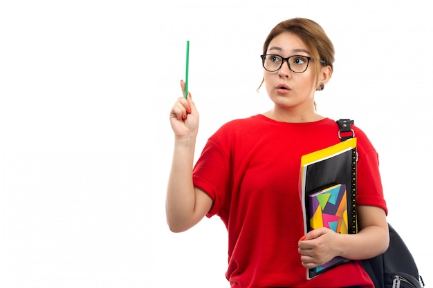 A front view young female student in red t-shirt black jeans holding different copybooks and files holding pencil thinking on the white