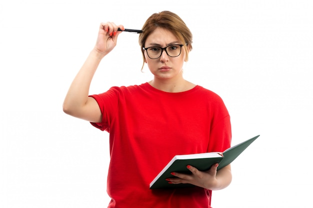 A front view young female student in red t-shirt holding copybook writing down notes thinking on the white