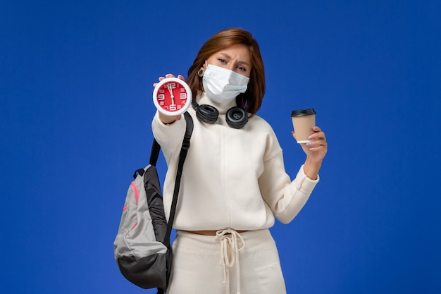 Front view young female student in white jersey wearing mask and backpack holding coffee and clock on blue wall