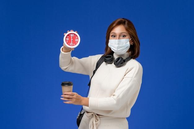 Vista frontale giovane studentessa in maglia bianca che indossa la maschera e zaino in possesso di caffè e orologio sulla parete blu