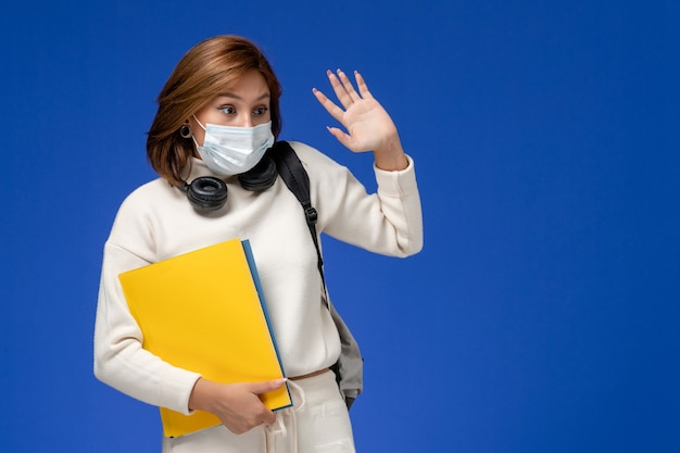 Front view young female student in white jersey wearing mask and backpack holding files on the blue wall