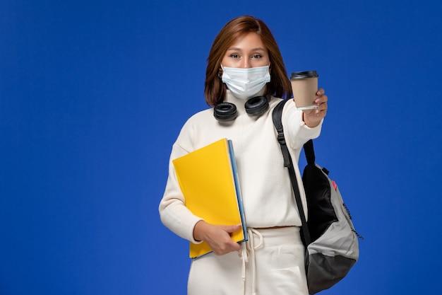Vista frontale giovane studentessa in maglia bianca che indossa la maschera e lo zaino che tiene file e caffè sulla parete blu