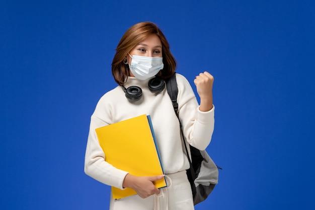 Vista frontale della giovane studentessa in maglia bianca che indossa la maschera e lo zaino che tengono i file che si rallegrano sulla parete blu