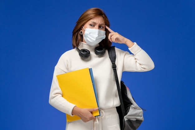 Front view young female student in white jersey wearing mask and backpack holding files and thinking on blue wall