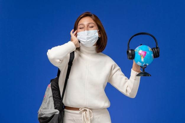 Vista frontale giovane studentessa in maglia bianca che indossa la maschera e zaino tenendo il globo con le cuffie sulla parete blu