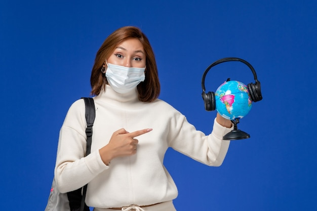 Front view young female student in white jersey wearing mask and backpack holding globe with headphones on blue wall