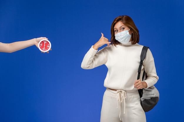 Vista frontale giovane studentessa in maglia bianca che indossa maschera e borsa sulla parete blu