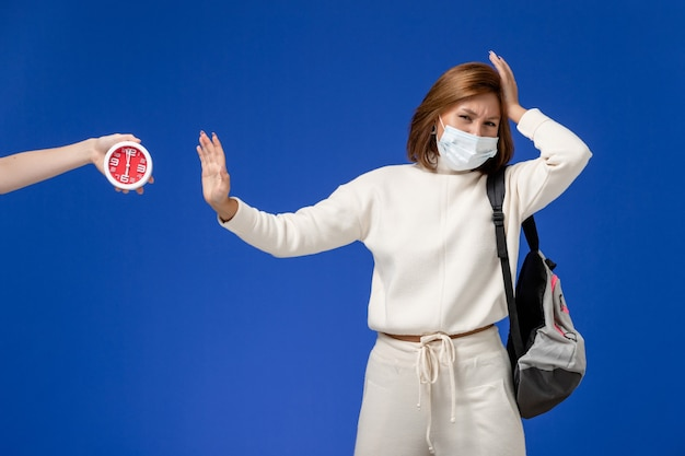 Front view young female student in white jersey wearing mask and bag on the blue wall