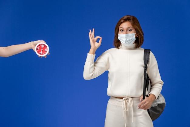 Vista frontale giovane studentessa in maglia bianca che indossa maschera e borsa che mostra bene il segno sulla parete blu